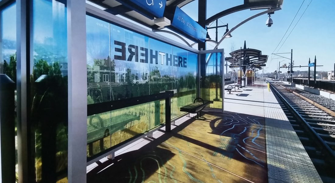 "(T)HERE, 2018 JW Clay Blue Line Station, Charlotte, NC Three windscreen areas of the station platform, playing with the relationship with the word ""here"" as the ground on which we stand and ""there"" in the horizon. Material: Laminated tempered glass and cement inlays. Dimensions: Glass windscreen, 8' x 20', platform area, 7' x 24' . Commissioning Agency: Charlotte Area Transit System (CATS) Photo credit: JoAnn Sieburg Baker"